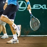 Feliciano tries to smack the rain soaked clay out of his sneakers.